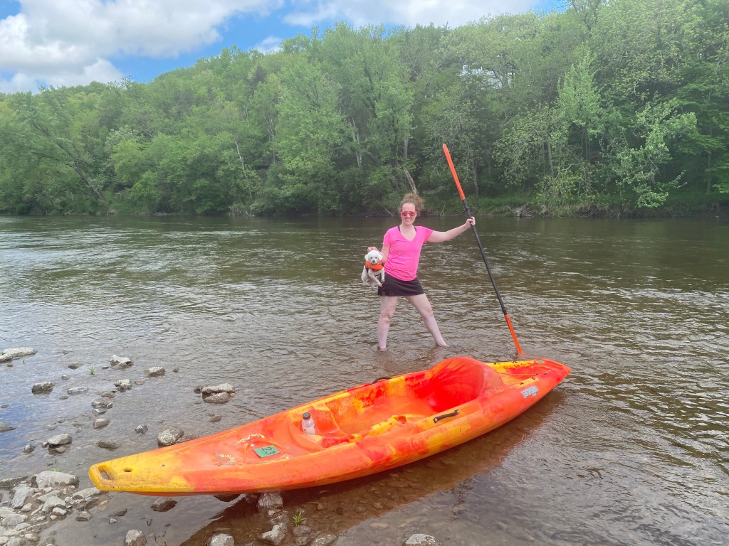 Keeya holding Quixote next to a kayak on a river